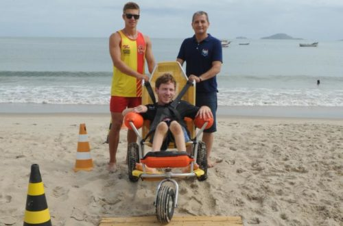 Cadeirante pronto para entrar no mar com os voluntários