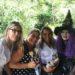 4 mulheres, sendo uma caracterizada de bruxa em um local aberto com árvores ao fundo