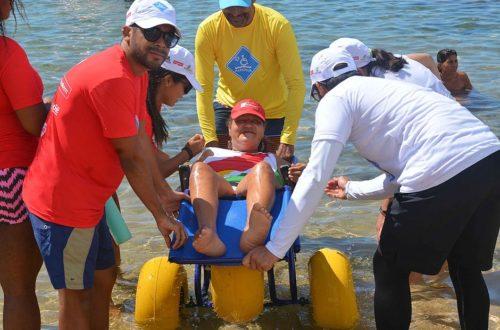Cadeirante entrando no mar com ajuda de voluntários
