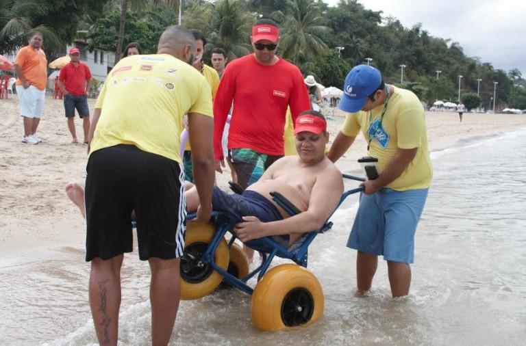 Voluntários auxiliando o deficiente a entrar no mar com cadeira adaptada