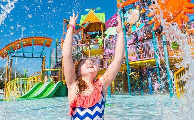 criança brincando com a agua e ao fundo vários brinquedos aquáticos