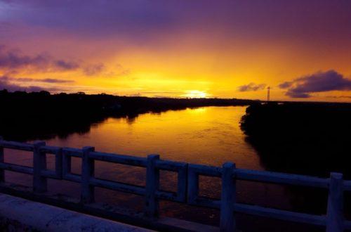 Pôr do Sol vista no rio Itacaiúnas com cores misturadas de amarelo, vermelho, laranja, lilás e roxo.