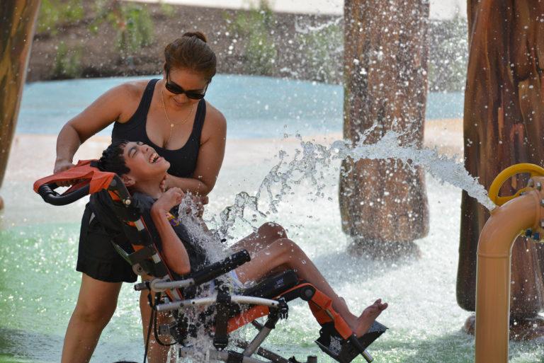 criança na cadeira especial brincando com adulto no brinquedo aquatico