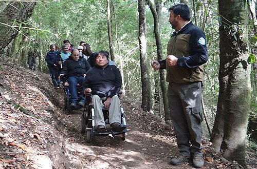 Monitor com visitantes cadeirantes na trilha
