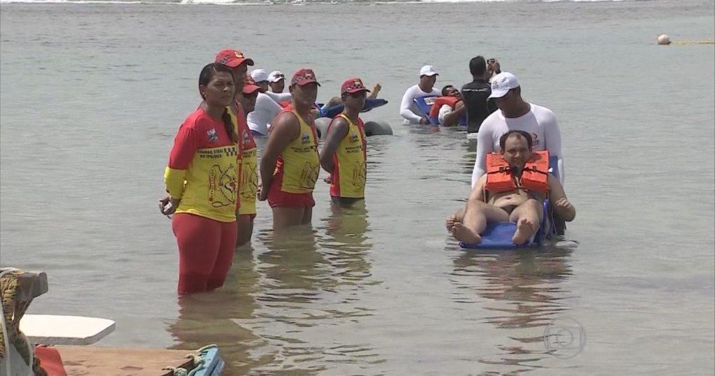 Cadeirante tomando banho de mar com ajuda dos salva vidas