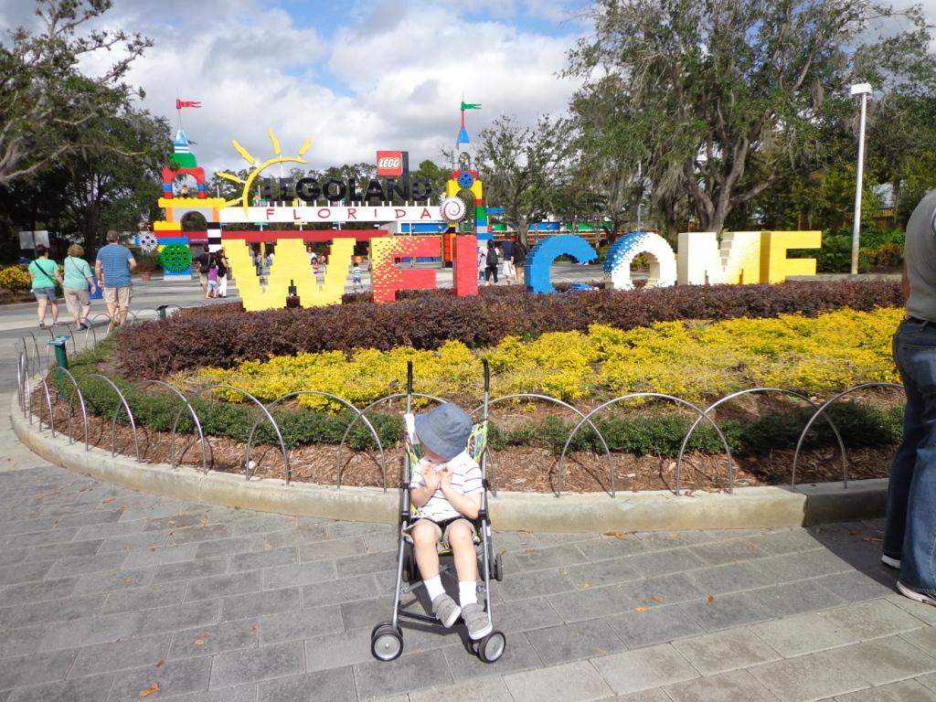 Entrada do Parque Legoland com a frase Welcome e uma criança no carrinho ao centro