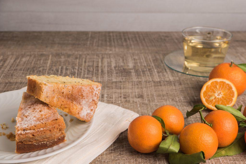2 pedaços cortados de Bolo de mexerica com as frutas na lateral direita e uma xícara de chá