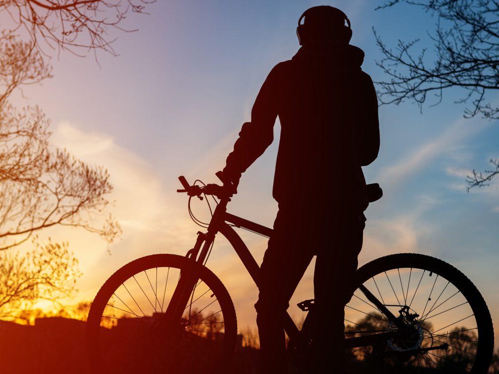 Ciclista apoiado na bicicleta curtindo o pôr-do-sol.