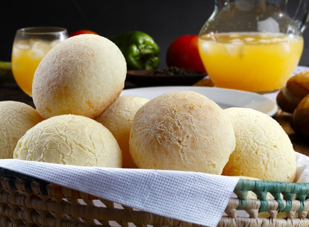 Cesta de pão de queijo na frente e atrás jarra e copo com suco de laranja