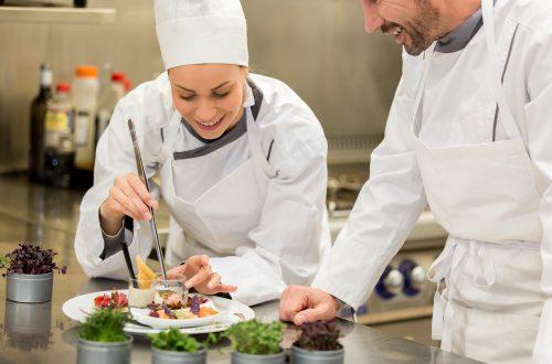 Dois chefs de cozinha preparando e decorando o prato para ser servido