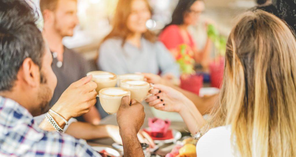 Amigos fazendo um brinde com xicara de café