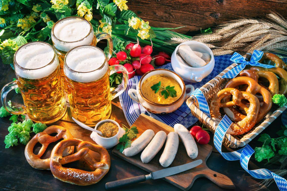 Vários quitutes da culinária alemã, como salsicha branca, pretzel, mostarda, cerveja sobre a mesa rústica