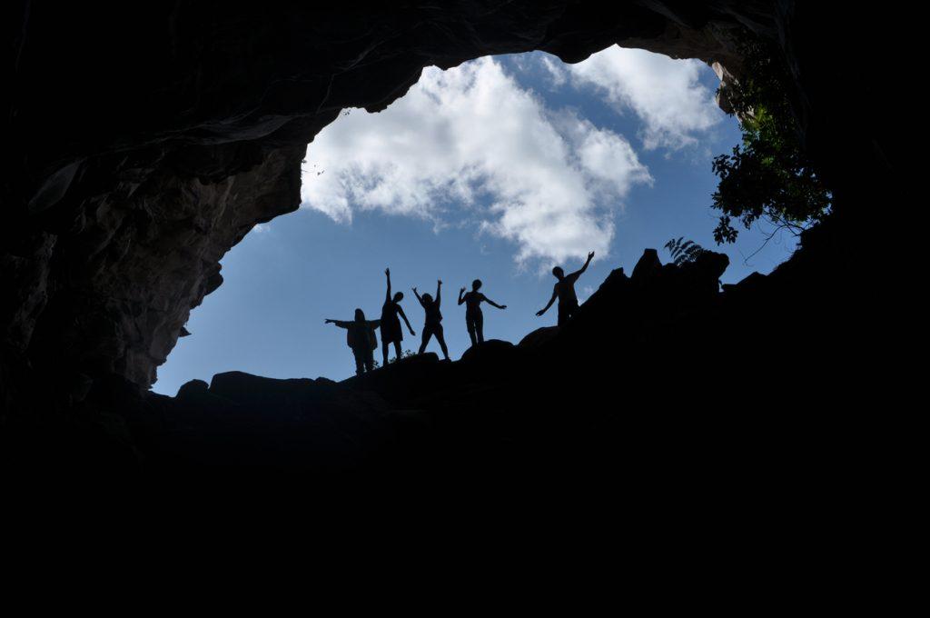 Foto tirada de dentro para fora da caverna e Várias pessoas fazendo pose aparecendo apenas a silhueta