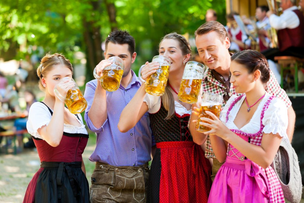 Vários mulheres caracterizadas com roupas da Alemanha ao lado de homens sorrindo e bebendo cerveja
