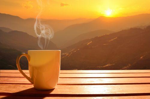 Xícara do café e o nascer do sol ao fundo