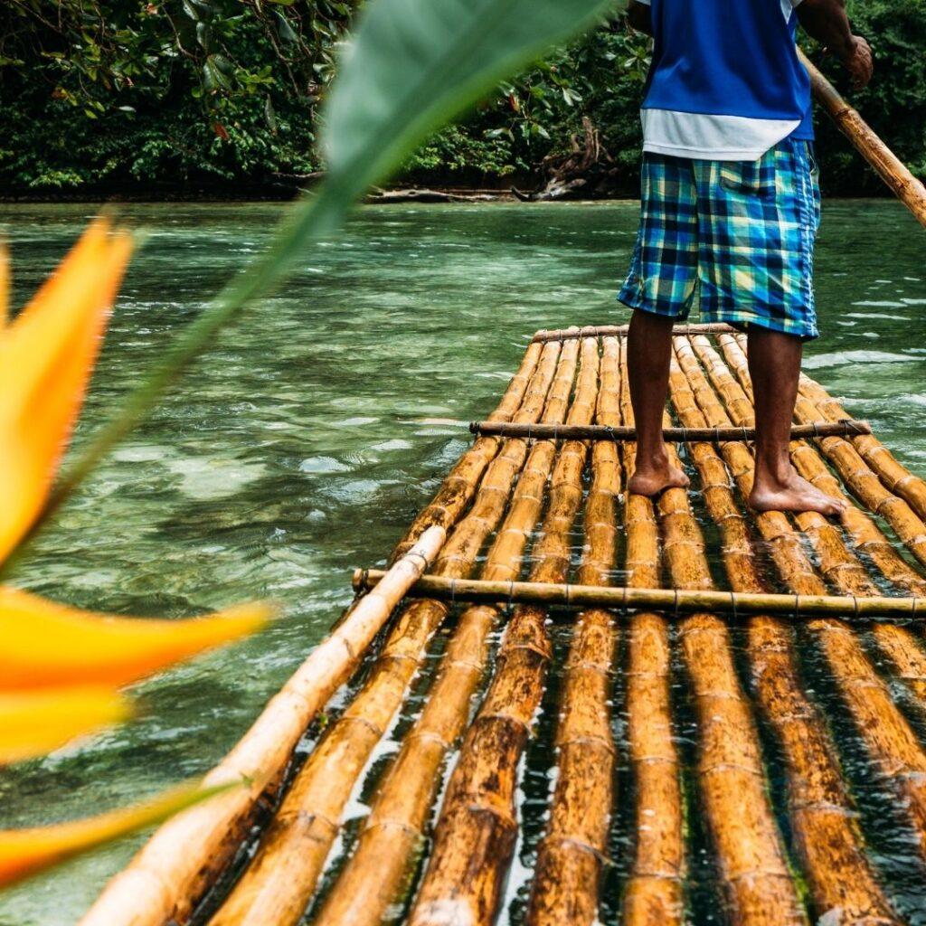 Homem guiando a jangada de bambu pelo rio Martha Brae